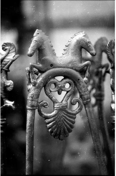 Vue de détail d'un décor de deux chevaux des quatre pieds de tabouret ou tablette en métal.