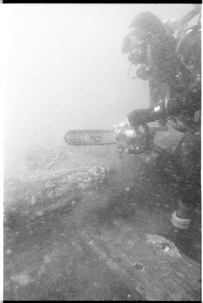 Vue sous-marine d'un plongeur effectuant un prélèvement sur la carène (fouille M. L'Hour/Drassm).