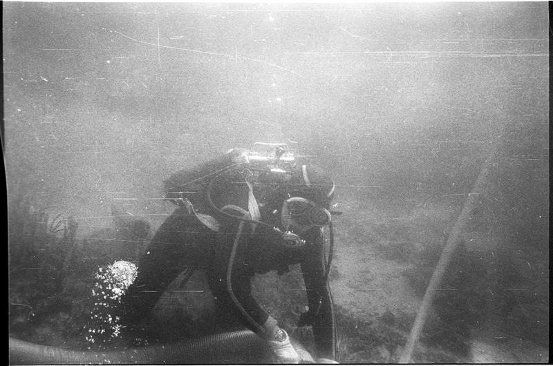 Vue sous-marine d'un plongeur dévasant à la suceuse à eau (fouille L. Long/Drassm).
