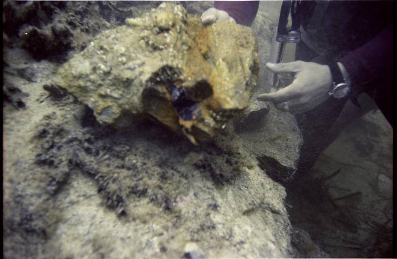 Vue sous-marine d'un plongeur et d'un fragment de concrétion métallique (fouille L. Long/Drassm).