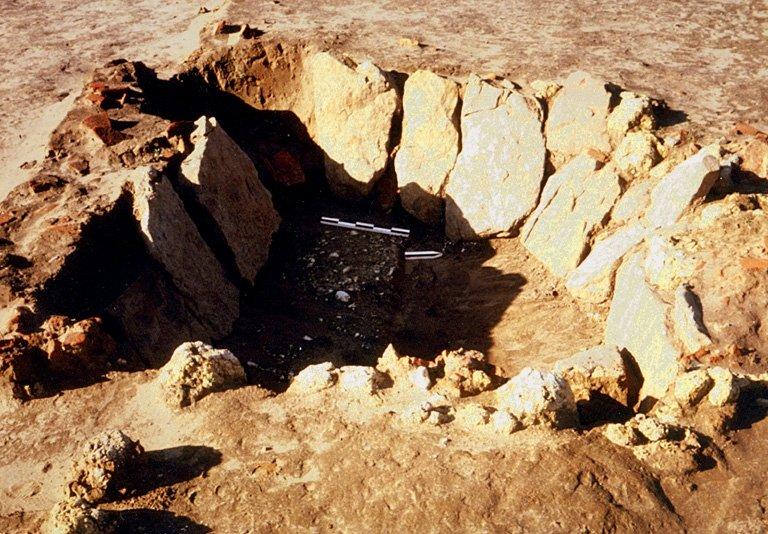 Structure 1076. L'appareillage de cette fosse aménagée, profonde de 0,95m est constituée de grandes dalles de grès inclinées, posées de champ. Un creusement dans l'angle sud-ouest, avec une tuile servant de marchepied, permet d'y accéder. Le sol épais de quelques cm est constitué d'un épandage de petits blocs de craie tassés.