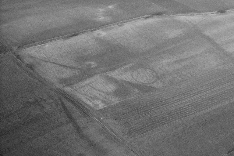Terrassements assez importants correspondant peut-être à des retranchements arasés. Vers les Hériez, grand enclos circulaire, larges tâches et lignes ouvertes enchevêtrées. On distingue également une voie matérialisée par une large traînée sombre bordée de deux fossés parallèles.