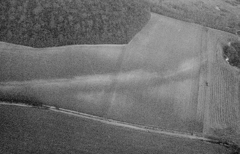 Traces de chaussée bombée et bordée de fossés se dirigeant vers le nord/nord-ouest.