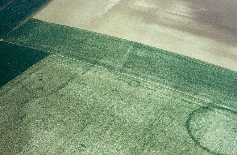 Ferme indigène matérialisée par des enclos curvilignes emboîtés. Grand enclos circulaire à petit pont d'entrée orienté au sud-sud-est, 3 petits enclos circulaires, tâches, points et lignes irrégulières.
