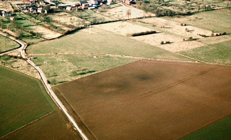 Sur le plateau, aire sombre d'habitat dans laquelle les prospections ont mis en évidence trois bâtiments, des tuiles, des rognons de silex, des clous. Occupation : fin du 1er s.-IIIe s.