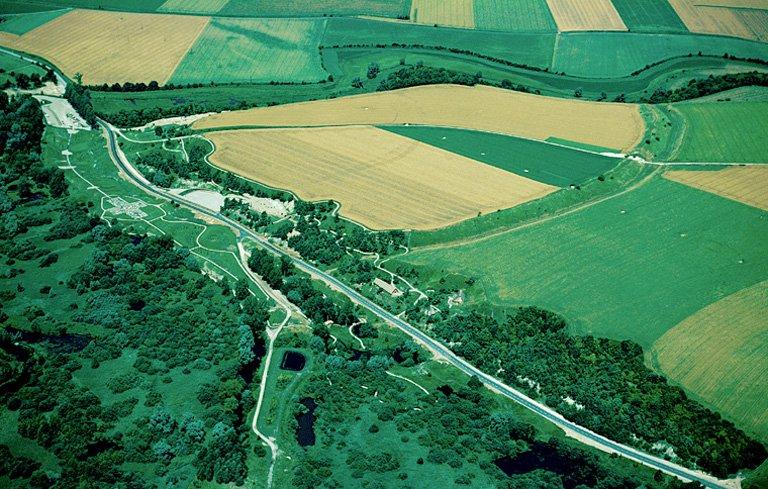"""A la confluence de deux rivières, sur la rive droite de la Somme, se trouve un oppidum (20 ha 25) qui domine, au nord la vallée sèche de Vaux (de 26 m), au sud, les pentes abruptes bordant la vallée tourbeuse qui s'étend jusqu'à la Somme (de 40 m environ), à l'ouest, la vallée d'Acon, dont l'altitude est de 22 m. Défendant un passage obligé des marais de la Somme, ici traversés par une levée de terre naturelle, il a été considéré comme """"Camp de César"""", dès le XVe siècle et improprement qualifié """"d'oppidum celtique"""" depuis la fin du XIXe siècle. Les fouilles récentes ont permis d'émettre l'hypothèse d'un """"camp retranché"""" établi après la guerre des Gaules, probablement par des auxilia de l'armée romaine."""