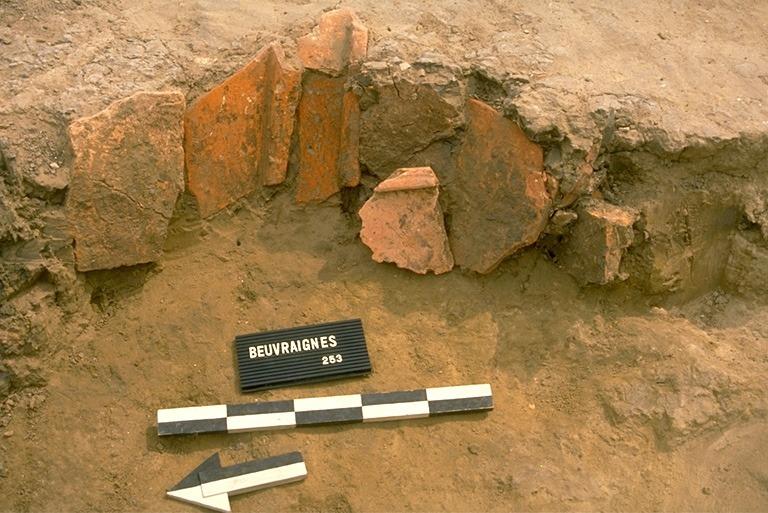 Structure 2049. Cette fosse présentant un creusement multiple. Une tuile posée verticalement est l'indice d'un aménagement des parois. Elle est comblée avec de l'argile grise avec débris de charbons de bois et terre cuite.