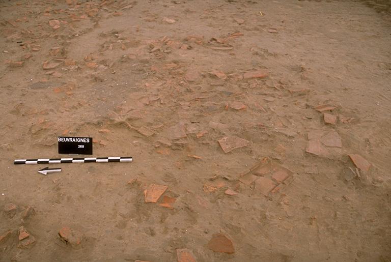 Structure 1055. Ce petit bâtiment ou galerie, protégé par une toiture en tuiles, a été retrouvée écroulé sur place. Sa fondation est matérialisée par un alignement de blocs de calcaire, de silex, et de grès.