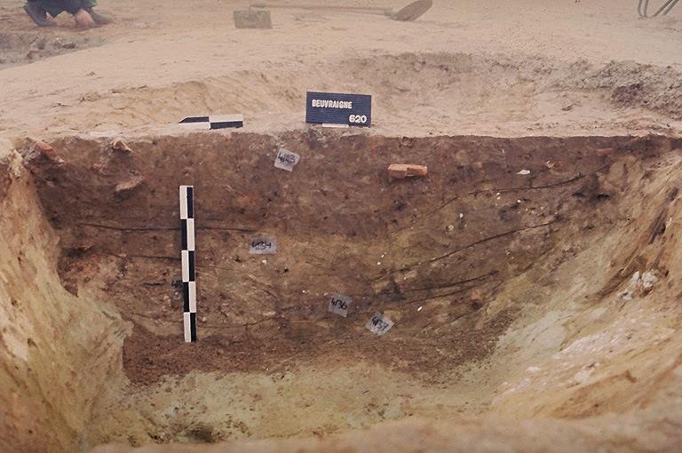 Structure 4103. Cette fosse est profonde de 0,60 m. Son bord sud est aménagé avec de la craie tassée. Elle est comblée avec de l'argile grise sableuse, un niveau de cendres et sable, une poche de mortier rose et silex, du sable contenant quelques granules de craie et de l'argile sablonneuse marron-brun et tuiles.