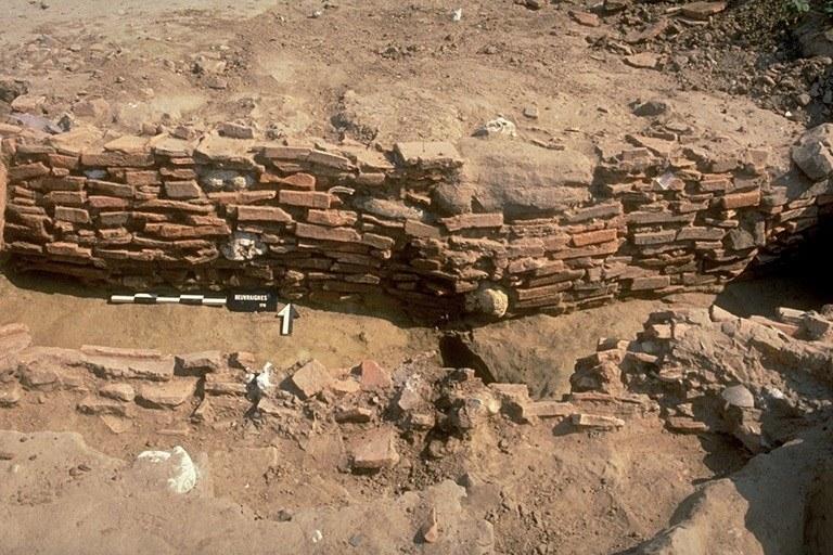Structure 1028. Le parement, maçonné en tuiles posées à plat, comprend aussi quelques grès dont certains renforcent l'angle nord-est, des silex, des blocs de craie, voire une meule entière réutilisée.