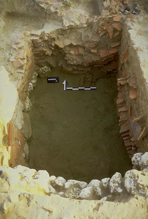 Structure 1087. Cette fosse aménagée, profonde de 1,20 m, est appareillée avec des tuiles ou des blocs calcaire tuiles reposant sur une fondation de grès, calcaire et silex.