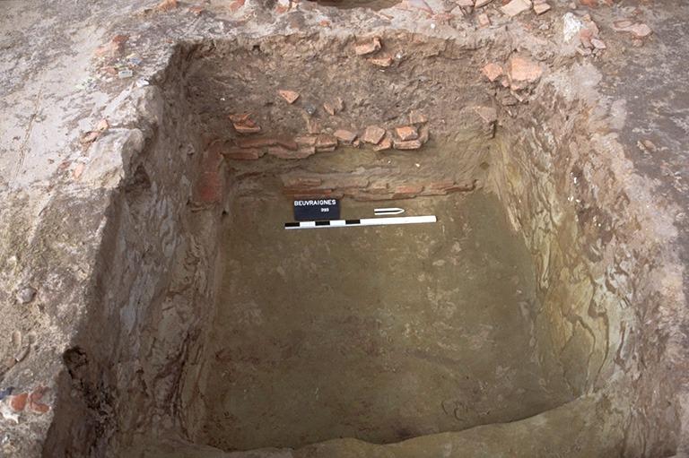 Structure 2099. Cette fosse aménagée a connu deux états successifs. Dans une première phase, elle a une forme carrée de 1,90 m de côté pour une profondeur de 1,35 m. 4 assises maximum de son appareillage en tuiles sont conservés sur la face ouest. Elle est ensuite recoupée par une fosse de forme rectangulaire de 2,75 x 2,20 m, moins profonde (0,92 m). Seule subsiste une assise du parement ouest, et, partiellement, une assise du parement sud.