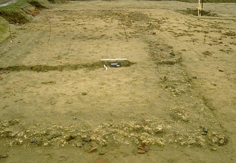 Structure 4015. Ces fondations correspondent à l'habitat du potier. Il comprend trois pièces édifiées, semble-t-il, en au moins deux états successifs. Au nord, la pièce 1 se distingue par une fondation de craie tassée et de silex relativement soignée et régulière. Le bâtiment s'agrandit ou est refait vers l'est avec des fondations de fragments de tuiles assez irrégulières avec quelques grès en renfort. Au sud de la maison, est accolé un appentis, probablement à claire-voie, qui ne se distingue que par quelques blocs de grès, notamment sur le côté sud. Les installations de tournage sont situées à proximité immédiate de la pièce 1.