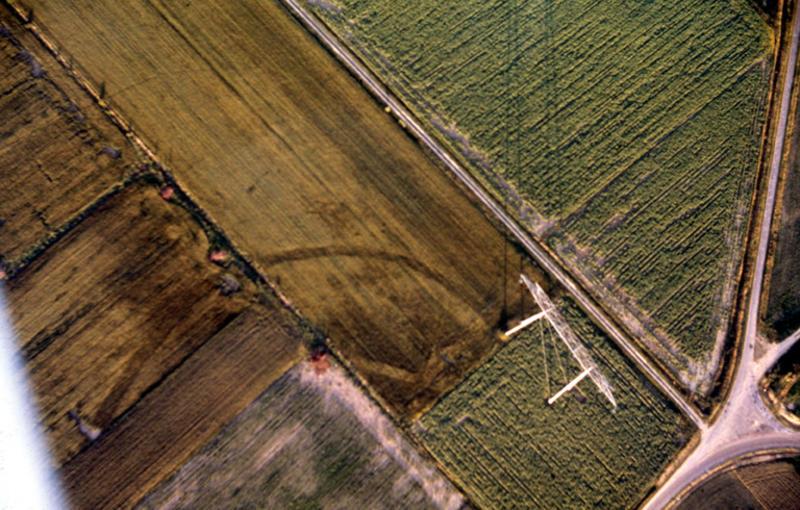 Grand enclos délimité par un fossé curviligne entrevus partiellement.