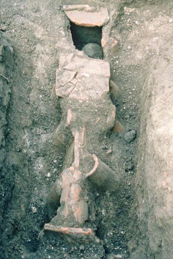 Vue de la tombe 1 orientée est-ouest, couverte par un coffrage de tuiles mixte.