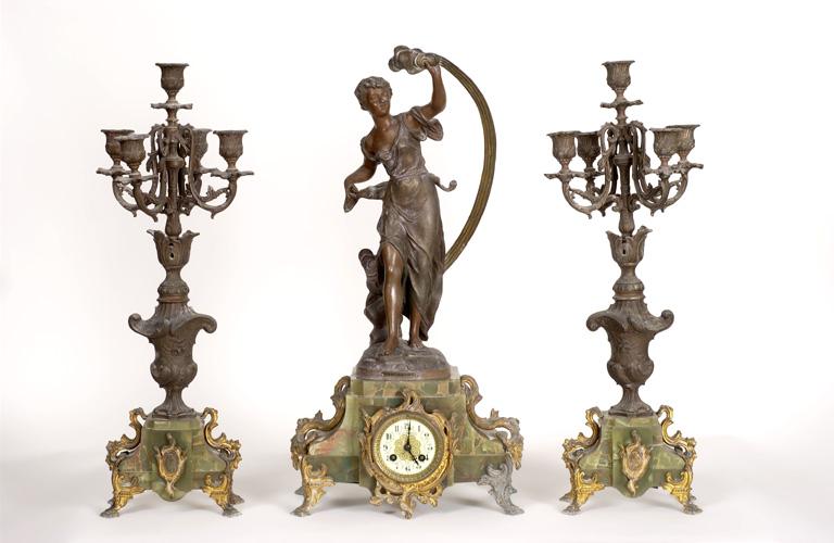 Garniture de cheminée composée de deux chandeliers et d'une pendule