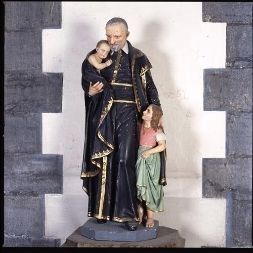 Groupe sculpté : Saint Vincent de Paul portant un bébé et abritant une petite fille
