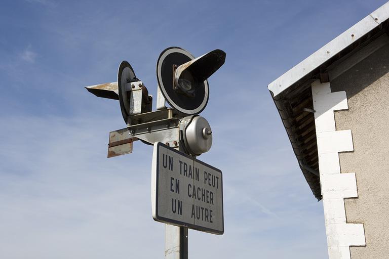 3 signaux lumineux, 2 panneaux de signalisation et 2 cloches (signaux sonores)