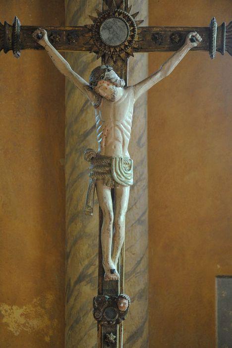 Croix de procession ornée d'un Christ nimbé de soleil avec à ses pieds deux angelots