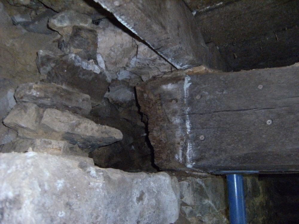 La poutre atteinte par la mérule, photo prise juste après le traitement (la partie de la poutre atteinte a été enlevée; en outre la poutre et le mur ont été imbibés de fongicides introduits par les petits trous visibles notamment sur la poutre).