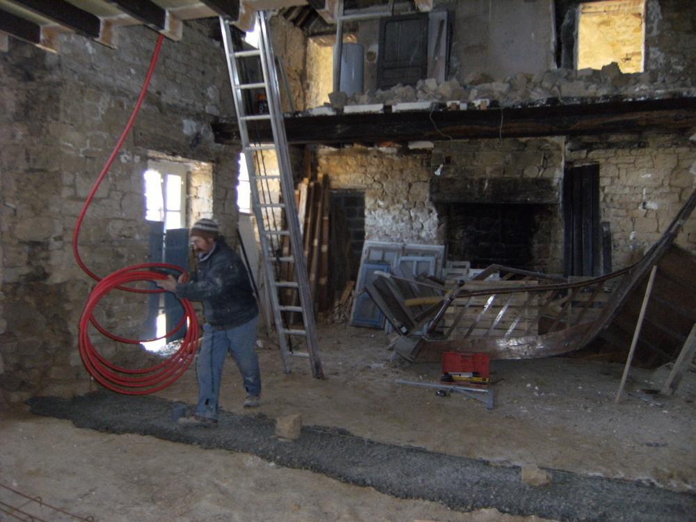 13 décembre 2010, installation de tubes et de conduits dans le mur de refend à remonter.