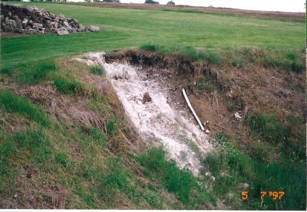 5 juillet 1997, le recul de la douve Nord est illustré par la longueur du drain désormais déterré (les traces blanches sont de la chaux versée là par le maçon qui restaurait alors le mur allant du manoir à son fournil).