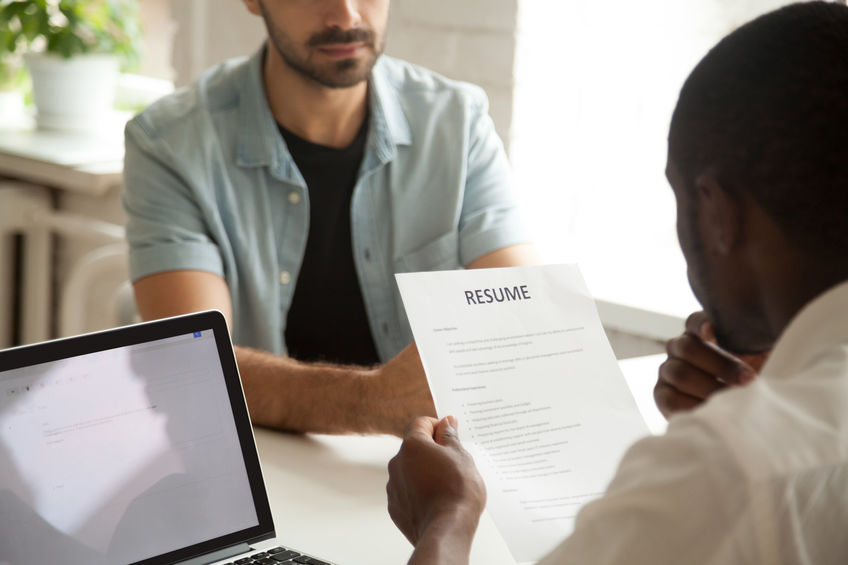 African-american hr manager holding reading applicants resume at
