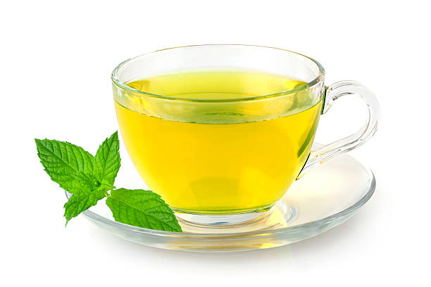 A glass cup of fresh mint tea on white background